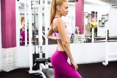 Binnenportret mooi sexy meisje in sportkleding in gymnastiek Royalty-vrije Stock Foto's