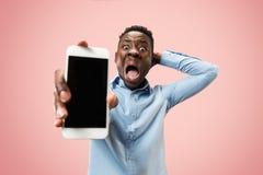 Binnenportret van de aantrekkelijke jonge zwarte mens die lege smartphone houden stock foto