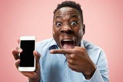 Binnenportret van de aantrekkelijke jonge zwarte mens die lege smartphone houden stock foto's