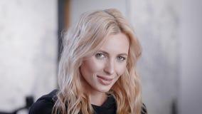 Binnenportret van een fantastische blondevrouw op middelbare leeftijd na zitting in een schoonheidssalon stock video