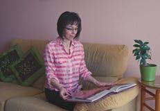 Binnenportret van glimlachende middenleeftijdsvrouw in gecontroleerd overhemd stock afbeeldingen