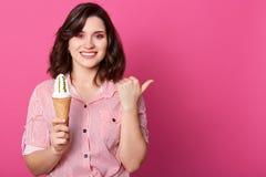 Binnenstudioschot van positieve mooie jonge vrouw status geïsoleerd over roze achtergrond, die roomijs in één hand, het maken hou royalty-vrije stock foto