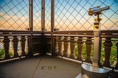 binocolo antico sulla torre Eiffel con un recinto del metallo durante il tramonto fotografia stock