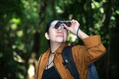 Binocolo di sguardo della donna di viaggio turistico sul nella foresta Fotografia Stock Libera da Diritti