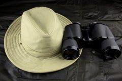 Binocolo e cappello su un cappotto all'aperto Immagine Stock