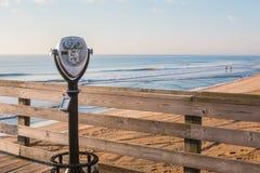 Binocolo facente un giro turistico sul pilastro e sulla spiaggia Fotografia Stock Libera da Diritti