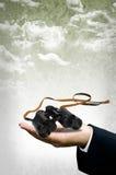 Binoculaire dans la main d'homme d'affaires, concept de vision Image libre de droits