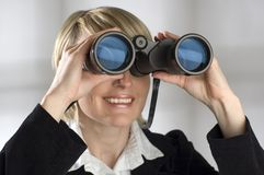 Binocular. Young blond women looking through binocular - business concept royalty free stock photography