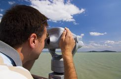 Binocular. Man look into metal binocular at beach stock photography