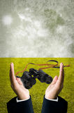 Binocular in businessman hand with field background Royalty Free Stock Images