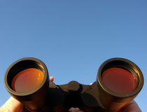 Binocular with Coated Lenses in Woman Hands. Binoculars with coated lenses in woman hands observing a sight in the distance over blue sky Royalty Free Stock Photography