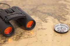 Binocular and compass on map Royalty Free Stock Photo