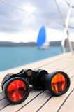 Binocular on the deck of yacht. Close up on binocular on deck of yacht with another yacht on horizon in natural blur stock image