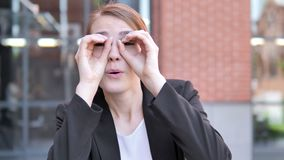 Binocular gesture by young businesswoman stock video