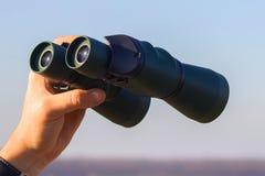 Binocular in mans hands Stock Photo