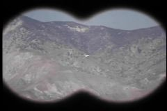 Binocular view of military airplane flying through mountains stock footage