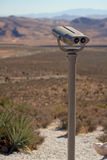 Binocular viewer overlooking desert Royalty Free Stock Photo