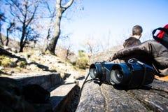 Binoculare nero su una tavola di legno durante la pausa di trekking immagine stock libera da diritti