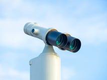 Binoculare stazionario contro chiaro cielo blu Fotografie Stock