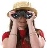 Binoculars. Girl with a straw hat looking at the camera through binoculars Royalty Free Stock Image
