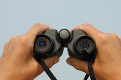 Binoculars. Pair of hands holding a pair of binoculars against a blue sky with lots of space for copy stock image