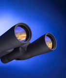 Binoculars. Black binoculars against a blue background with sky reflection Royalty Free Stock Photos