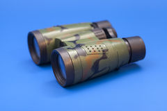 Binoculars on blue background. Isolated Royalty Free Stock Images