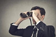 Binoculars. Businessman looking at something through a binoculars stock photography