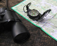 Binoculars and a Compass on the Map during hiking. Royalty Free Stock Images