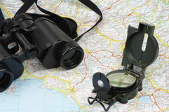 Binoculars, compass and map Stock Images