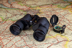 Binoculars and Compass on Old Route Map Royalty Free Stock Photography