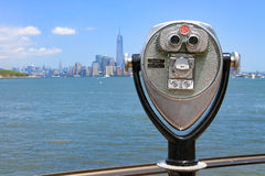 Binoculars in Ellis Island and Manhattan's skyline in the backgr Royalty Free Stock Image