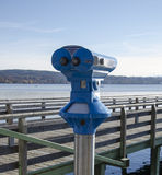 Binoculars, exploration, wooden bridge, mountainous shores, lake. Powerful binoculars for exploration in front of a lake with wooden bridge and mountainous royalty free stock images
