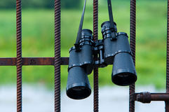 Binoculars hanging on metal grating Royalty Free Stock Images