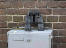 Binoculars left on a fuse box or meter cabinet against a brick wall. Some binoculars left on a fuse box or meter cabinet against a brick wall royalty free stock photography