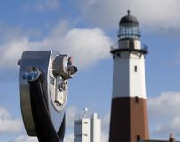 Binoculars and lighthouse. Pay Binoculars on the beautiful sky and lighthouse background Royalty Free Stock Images