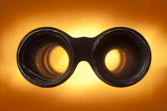 Binoculars. Looking through antique binoculars on a sunburst background Royalty Free Stock Photos