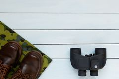 Binoculars and male shoes on a wooden background. Binoculars and male shoes on a blue wooden background Royalty Free Stock Photo