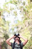 Binoculars - man hiker looking up. At copy space during outdoors hiking trip Royalty Free Stock Photo
