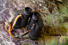 Binoculars with map. Binoculars on terrain photo map Royalty Free Stock Images