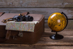 Binoculars and map on suitcase. Stock Photos