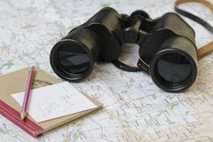 Binoculars and notebook are on the tourist map stock photos
