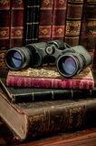 Binoculars and old books Stock Photography