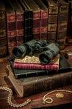 Binoculars and old books Stock Image