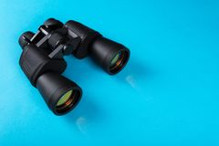 Binoculars with orange lens on blue background stock photos
