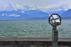 Binoculars and panoramic view of lake and mountains Royalty Free Stock Photography