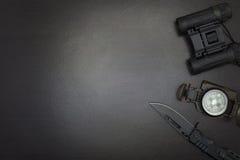 Binoculars, pocket knife,compass,on dark wood background. Binoculars, pocket knife,compass,on dark wood background Stock Photography
