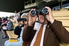Binoculars at racing. Spectators watch a horse race with binoculars from the stands Stock Photography
