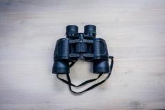 Binoculars on the table. Black binoculars on a wooden table Royalty Free Stock Image