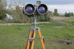 A binoculars with a tripod with a azimuth head in a forest on a sand with grass Stock Image